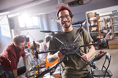 Portrait smiling male designer holding drone in workshop - p1023m1486410 by Agnieszka Olek