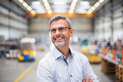 Portrait of a happy mature businessman in a factory - p300m2188440 by Daniel Ingold