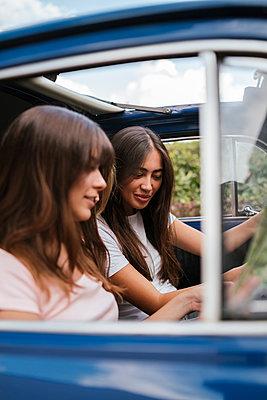 Friends reading route map inside car - p429m2097346 by Lorenzo Antonucci