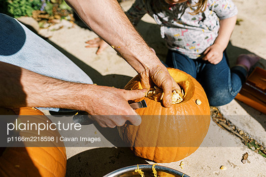 Little girl carving out pumpkins for halloween with her dad - p1166m2218598 by Cavan Images