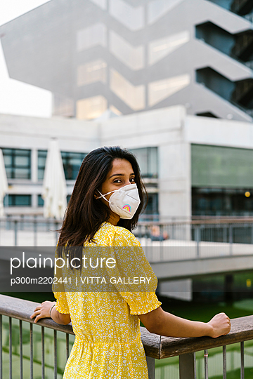 Young woman wearing face mask while standing on elevated walkway in city - p300m2202441 by VITTA GALLERY