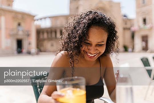 Happy woman holding juice glass at sidewalk cafe - p300m2202557 by Ezequiel Giménez