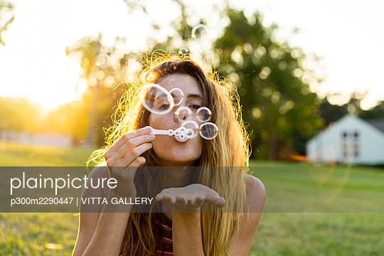 Young woman blowing bubbles at park - p300m2290447 by VITTA GALLERY