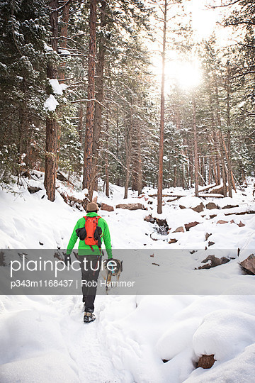 A guy and his dog hiking on a snowy trail. - p343m1168437 by Rob Hammer