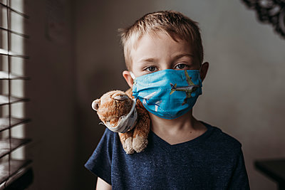Close up of young school aged boy with mask on with stuffed animal - p1166m2207797 by Cavan Images