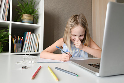 Laughing girl sitting at table at home doing homework and using laptop - p300m2154867 by Ekaterina Yakunina