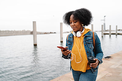 Young woman using smart phone while walking at the waterfront - p300m2266410 by COROIMAGE