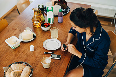 Woman checking diabetes while having breakfast on table at home - p426m1537130 by Maskot