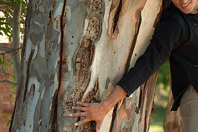 Man touching tree trunk, cropped - p624m727304f by Michele Constantini