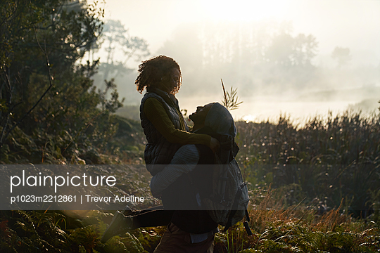 Silhouette affectionate young couple hiking in nature - p1023m2212861 by Trevor Adeline