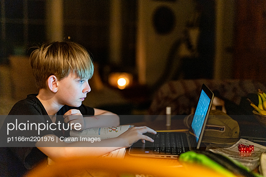 Young person working on laptop while distance learning in the evening - p1166m2201976 by Cavan Images