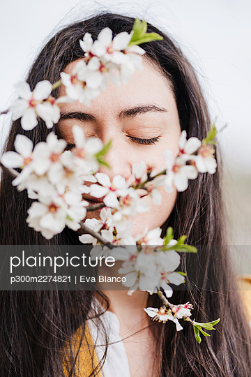 Mid adult woman with eyes closed smelling flowers - p300m2274821 by Eva Blanco