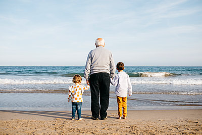 Back view of grandfather standing hand in hand on the beach with his grandchildren watching the sea - p300m2103163 von Josep Rovirosa