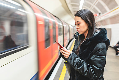 Portrait of woman waiting at underground station platform looking at smartphone, London, UK - p300m2167636 by William Perugini