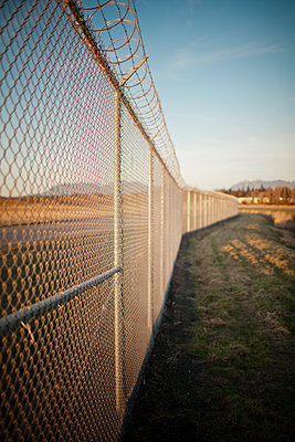 Chain-linked fence with a barbed wire finish. - p343m1101615f by Christopher Kimmel