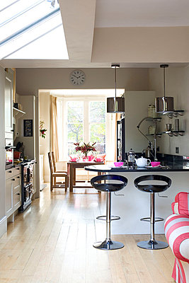 Black bar stools at breakfast bar of open plan London kitchen with skylight  UK - p3493533 by Robert Sanderson