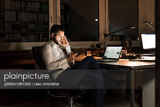 Businessman using tablet in office at night - p300m1581305 by Uwe Umstätter