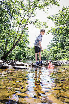 Boy on the riverbank holding spoon net - p1019m1462175 by Stephen Carroll