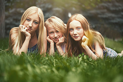 Portrait beautiful sisters laying in grass - p1023m2088079 by Arman Zhenikeyev