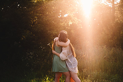 Lesbian couple embracing in forest during summer - p1166m2212450 by Cavan Images