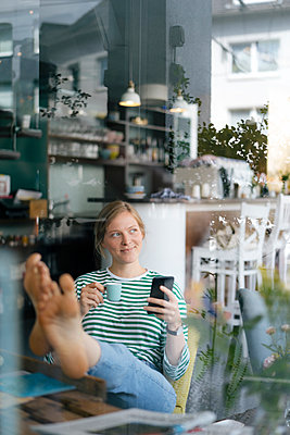 Smiling young woman with feet up holding cell phone and espresso cup in a cafe - p300m2059107 by Kniel Synnatzschke