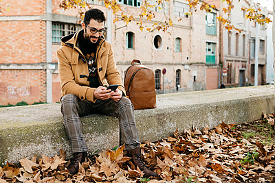 Spain, Igualada, smiling man sitting down using cell phone in the autumnal town - p300m2080702 by Josep Rovirosa