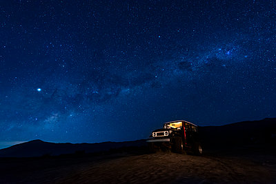 Indonesia, East Java, Milky Way galaxy on blue starry night sky over car parked in Bromo Tengger Semeru National Park - p300m2155857 by Torsten Velden