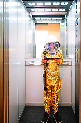 Boy wearing space suit playing video game while standing in open elevator - p300m2221357 by Jose Luis CARRASCOSA