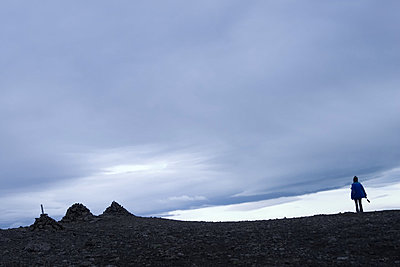 Person walking, three cairns on the side, grey sky above.  Laki, South Iceland. - p34810572 by Bjarki Reyr Asmundsson