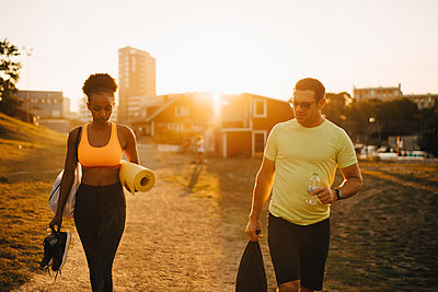 Male and female athlete walking together on land during sunset - p426m2270556 by Maskot