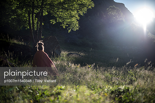 People meditating in the grass of a field at sunrise - p1007m1540348 by Tilby Vattard
