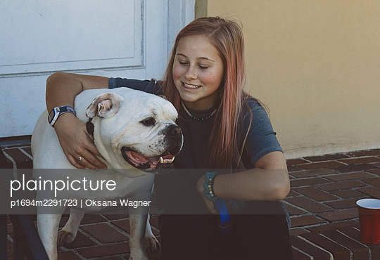 Happy girl cuddling with her dog before going for a walk - p1694m2291723 by Oksana Wagner