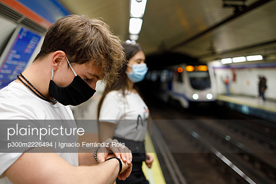 Young man checking time while standing by woman with social distance at subway platform - p300m2226494 by Ignacio Ferrándiz Roig