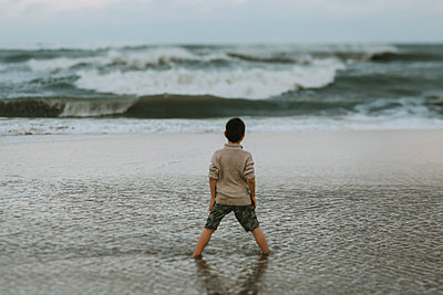 Rear view of boy standing in sea against sky during sunset - p1166m2034801 by Cavan Images