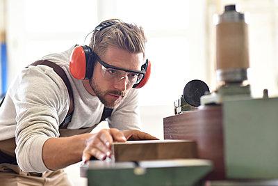 Carpenter using belt sander in his workshop - p300m1192393 by lyzs