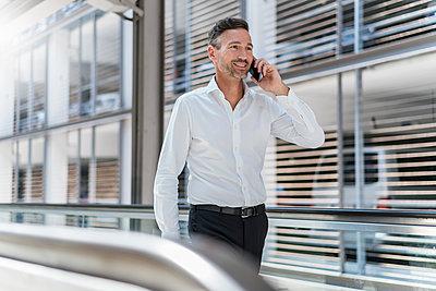 Businessman on escalator talking on the phone - p300m2140225 von Daniel Ingold