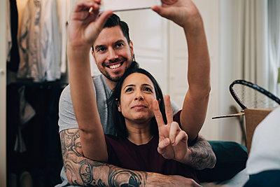Loving couple taking selfie on mobile phone in bedroom - p426m1542753 by Maskot