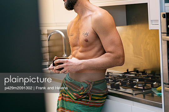 Hipster man having coffee in kitchen - p429m2091302 by Frank and Helena