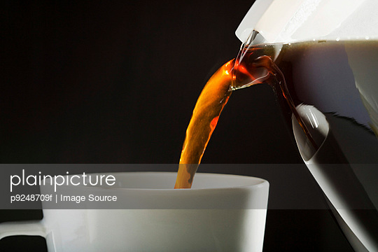 A cafetiere pouring coffee into cup - p9248709f by Image Source