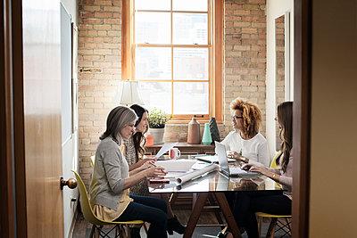 Multi-ethnic creative businesswomen discussing in board room - p1166m1141469 by Cavan Images