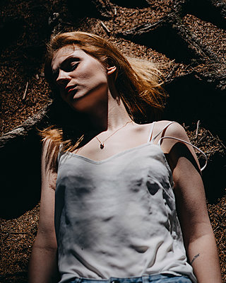 Young woman lies on forest floor - p1184m1424551 by brabanski