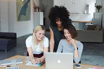 Drei junge, moderne Frauen besprechen lächelnd eine Idee am Laptop in einem modernen Büro  - p1301m2021034 von Delia Baum