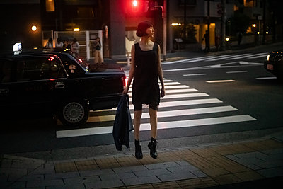 Asian teenage girl strolling in town at night - p1321m2223376 by Gordon Spooner