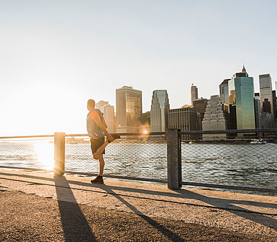 USA, Brooklyn, man doing stretching exercises in front of Manhattan skyline in the evening - p300m1206270 by Uwe Umstätter