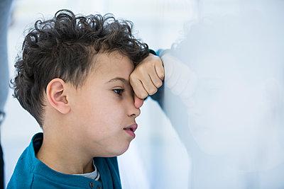Stressed schoolboy leaning against whiteboard in class - p300m2004522 von Fotoagentur WESTEND61