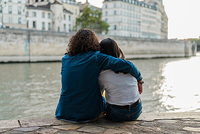 France, Paris, rear view of young couple sitting on a wall at river Seine - p300m2023890 von VITTA GALLERY