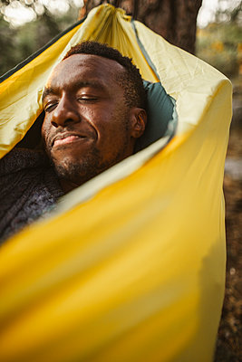 Man sleeping in hammock at forest - p426m2218752 by Maskot