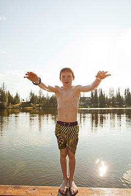 Caucasian boy falling backwards into lake - p555m1411544 by John Lee