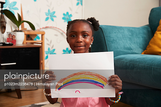 Portrait cute girl holding rainbow drawing in living room - p1023m2238478 by Himalayan Pics