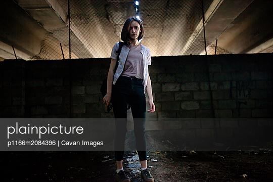 Woman stands under a big bridge - p1166m2084396 by Cavan Images